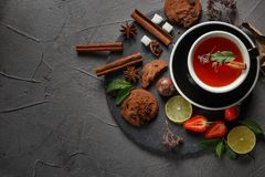 Fragrant tea in a black cup on a black plate with biscuits, lemon, cinnamon and fruits. Cookies strawberries lime ieta sugar fresh food dark glass healthy royalty free stock photos