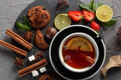 Fragrant tea in a black cup on a black plate with biscuits, lemon, cinnamon and fruits. Cookies strawberries lime ieta sugar fresh food dark glass healthy royalty free stock photography