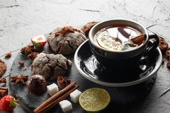 Fragrant tea in a black cup on a black plate with biscuits, lemon, cinnamon and fruits. Cookies strawberries lime ieta sugar fresh food dark glass healthy stock image