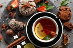 Fragrant tea in a black cup on a black plate with biscuits, lemon, cinnamon and fruits. Cookies strawberries lime ieta sugar fresh food dark glass healthy stock photos