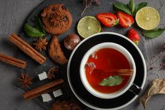 Fragrant tea in a black cup on a black plate with biscuits, lemon, cinnamon and fruits. Cookies strawberries lime ieta sugar fresh food dark glass healthy stock images