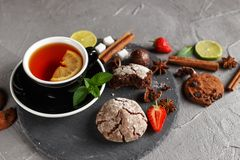 Fragrant tea in a black cup on a black plate with biscuits, lemon, cinnamon and fruits. Cookies strawberries lime ieta sugar fresh food dark glass healthy royalty free stock images