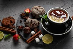 Fragrant tea in a black cup on a black plate with biscuits, lemon, cinnamon and fruits. Cookies strawberries lime ieta sugar fresh food dark glass healthy stock photo