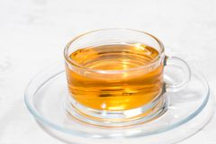 Fragrant tea in a glass cup on a white background, closeup. Horizontal Stock Image
