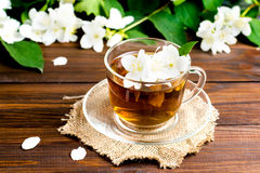 Fragrant tea with jasmine in a glass cup on a wooden table. Jasmine flowers Royalty Free Stock Images
