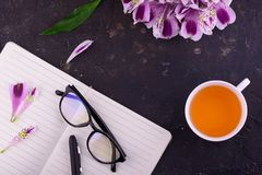 Fragrant tea in a white cup, beautiful flowers, a black background, a notebook with a pen and glasses. View from above. Fragrant tea in a white cup, beautiful stock image