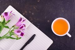 Fragrant tea in a white cup, beautiful flowers, a pink background, a notebook with a pen and glasses. View from above. Fragrant tea in a white cup, beautiful royalty free stock images