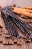 Fragrant vanilla, cinnamon sticks and coffee grains on wooden surface Stock Images