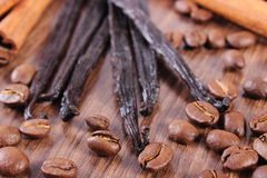 Fragrant vanilla, cinnamon sticks and coffee grains on wooden surface Royalty Free Stock Photo