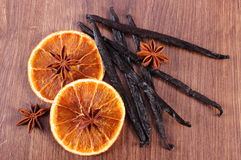 Fragrant vanilla, star anise and dried orange on wooden surface plank Stock Images