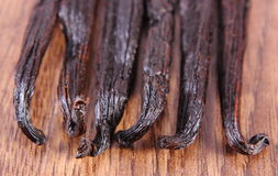 Fragrant vanilla sticks on wooden surface plank Stock Photos