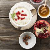 Fragrant warm homemade rice milk porridge with sugar and pomegranate seeds on a wooden background. The concept of. Healthy, seasonal dishes. selective focus Royalty Free Stock Photos