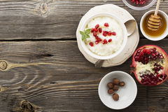 Fragrant warm homemade rice milk porridge with sugar and pomegranate seeds on a wooden background. The concept of. Healthy, seasonal dishes. selective focus Royalty Free Stock Images