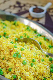 Fragrant yellow fried rice with green peas. Royalty Free Stock Photo