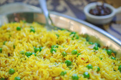 Fragrant yellow fried rice with green peas. Royalty Free Stock Images
