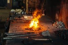 Fragua del herrero con las herramientas de la chimenea y del metal foto de archivo libre de regalías