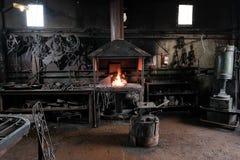 Fragua, trabajo del ` s del herrero, de fundición foto de archivo