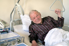 Frail senior man in a hospital bed Stock Images