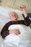 Frail senior man lying in a hospital bed Royalty Free Stock Photography