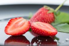 Frais de la demi fraise sur le plancher noir et le réflexe Photos libres de droits