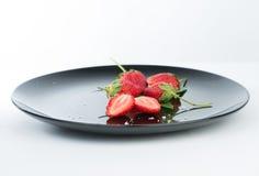 Frais de la demi fraise sur le plat noir et le réflexe Photo stock