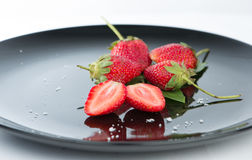 Frais de la demi fraise sur le plat noir et le réflexe Photographie stock