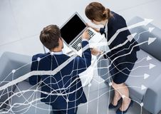 Frais généraux d'homme et de femme d'affaires avec l'ordinateur portable derrière le graphique blanc Image libre de droits