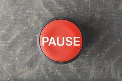 Frais généraux de bouton poussoir rouge de pause sur le fond concret images stock
