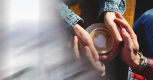 Frais généraux de deux paires de mains autour de tasse de café avec le coeur dans la mousse avec la transition blanche trouble Photo libre de droits