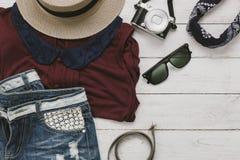 Frais généraux de l'accessoire à voyager avec le concept de fond d'habillement de femmes de mode Photos stock