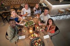 Frais généraux des amis heureux dinant ensemble Photos libres de droits