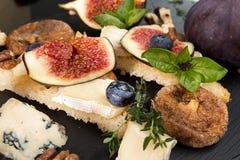 Frais généraux des figues, figues sèches, sandviches de casse-croûte avec le brie, c bleu Photos stock