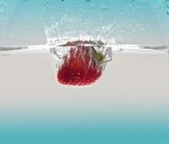 Fraise éclaboussant dans l'eau image stock