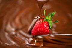 Fraise en chocolat Chocolat fondu versant sur le plan rapproché juteux mûr frais de fraise au-dessus du fond de brun de remous fo photo stock
