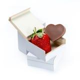 Fraise et chocolat en forme de coeur dans une boîte sur le fond blanc Photos stock