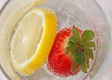 Fraise et citron dans un verre d'eau Image libre de droits