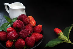 Fraise et laitier rouges mûrs frais sur une table noire Baies dispersées Un grand endroit pour le texte Photographie stock