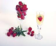 Fraise et un plein champagne en verre Photographie stock