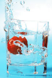 Fraise tombant dans un verre avec de l'eau Photo libre de droits