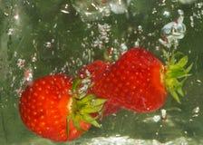 Fraises dans l'eau Photos stock