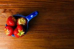 Fraises dans la cuvette bleue sur la table en bois de vintage Fraise juteuse rouge image libre de droits