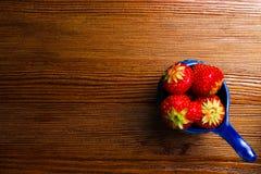 Fraises dans la cuvette bleue sur la table en bois de vintage Fraise juteuse rouge photographie stock