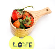 Fraises dans la tasse en bois avec la note d'amour Images stock