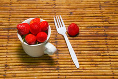 Fraises dans la tasse, fond de rotin, foyer choisi au strawberri Photographie stock libre de droits