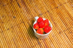 Fraises dans la tasse, fond de rotin, foyer choisi au strawberri Photographie stock