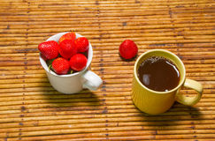 Fraises en tasse et café, fond de rotin, foyer choisi à Photographie stock