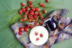 Fraises et un broc sur un tissu à carreaux dans un style rustique Image stock