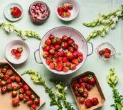Fraises fraîches dans la passoire, la confiture dans le pot en verre avec des fleurs d'été et les baies fraîches dans la boîte, l Image stock