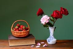 Fraises fraîches dans les paniers en osier et les roses Image libre de droits