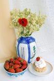 Fraises, gâteau et un vase avec des fleurs Photos stock